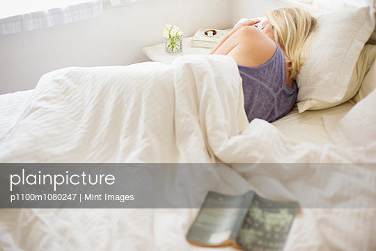 Blonde woman sleeping in a bed with white linen. - p1100m1080247 by Mint Images