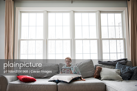 Wide View of Girl Home Sick From School On Couch With Tablet and Teddy - p1166m2191968 by Cavan Images