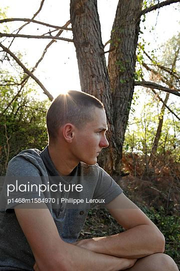 Jugendlicher sitzt nachdenklich im Freien - p1468m1584970 von Philippe Leroux
