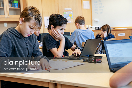 Boys using laptops at school - p312m2119729 by Johner