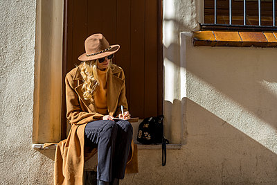 Fashionable young woman sitting at house entrance writing in notebook - p300m1562846 by VITTA GALLERY