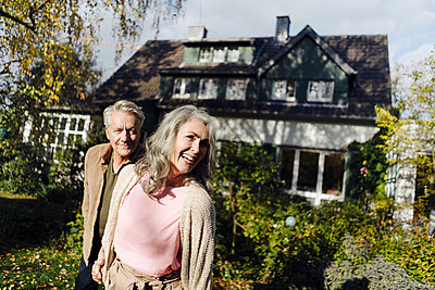 Happy senior couple in garden of their home in autumn - p300m2154985 by Gustafsson