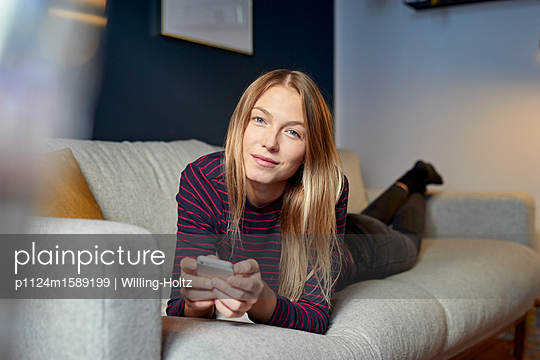 Young woman on sofa using smartphone - p1124m1589199 by Willing-Holtz