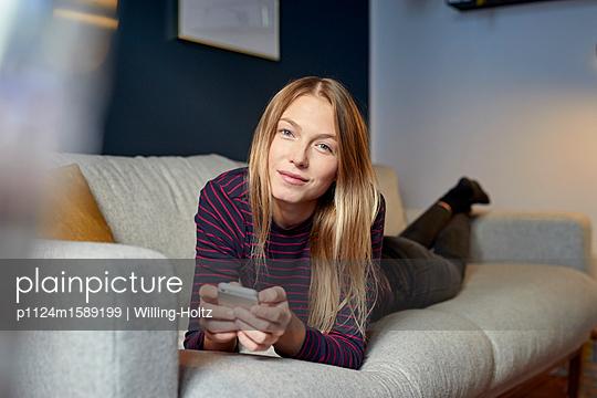 Junge Frau auf dem Sofa mit Smartphone - p1124m1589199 von Willing-Holtz