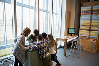 Curious children watching exhibit display in science center - p1192m1194215 by Hero Images