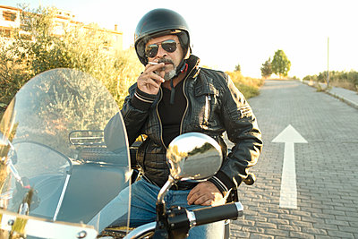 Portrait of cool biker wearing helmet and sunglasses sitting on his sidecar motorcycle smoking cigarette - p300m1191646 by Jaen Stock