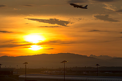 Commercial airplane setting off from airport at sunset - p300m2144192 by Konstantin Trubavin