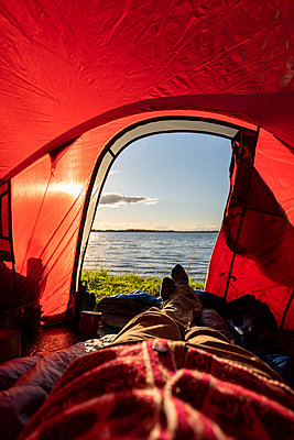 Man camping in Estonia, watching sunset lying in tent - p300m2219367 by Kike Arnaiz