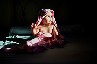 Cute baby girl in towel looking away while sitting on bed at home - p300m2221182 by Kiko Jimenez