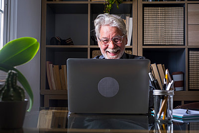 Happy senior businessman working on laptop at table in home office - p300m2277625 by Simona Pilolla