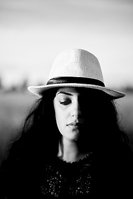 Portrait of black-haired woman with straw hat - p552m2287960 by Leander Hopf
