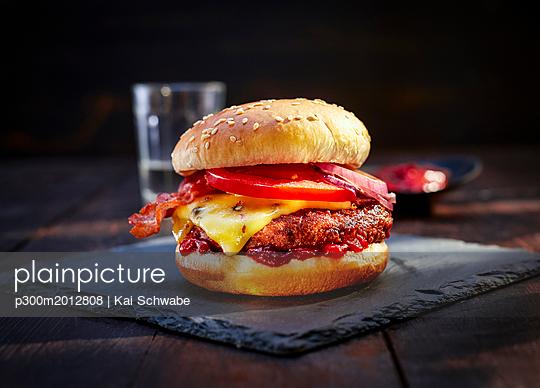 Cheeseburger with bacon on slate - p300m2012808 von Kai Schwabe
