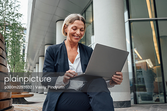Mature businesswoman working on laptop at office park - p300m2293932 by Vasily Pindyurin