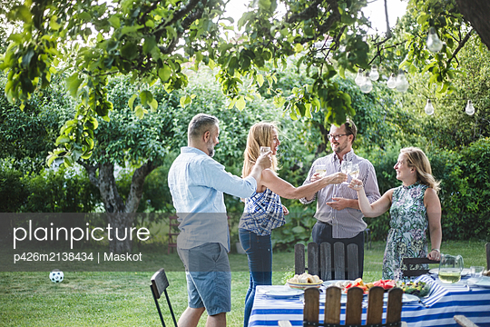 Happy friends clinking wine glass while standing in backyard during weekend party - p426m2138434 by Maskot
