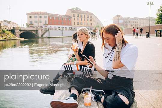 Three young women sitting on a riverbank, drinking and using mobile phone. - p429m2202292 by Eugenio Marongiu
