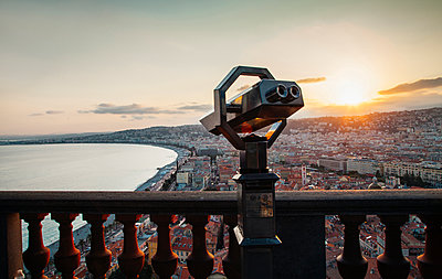 Coin-operated binoculars by balusters against cityscape and sky during sunset - p1166m2001372 by Cavan Images