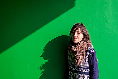 Young woman leaning on a green wall smiling - p1166m2072182 by Cavan Images