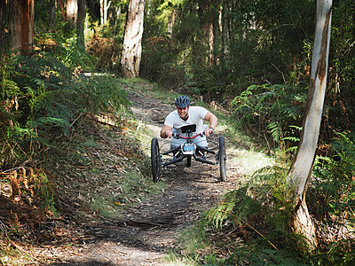 Man riding modified bicycles on forest path - p555m1304831 by PhotoAbility