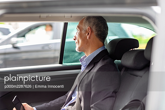 Senior businessman sitting in the back of car looking out of the window; Florence, Italy - p300m2287626 von Emma Innocenti