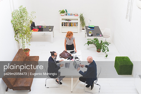 Businessmen and woman using laptops at office meeting, high angle view - p429m2058473 by Eugenio Marongiu