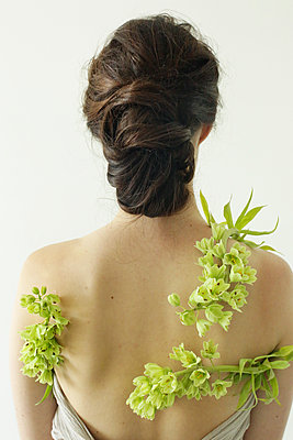 Portrait of a woman with brown hair tied in an elegant bun, wearing a dress with a green flower wreath. - p1100m1080248 by Mint Images