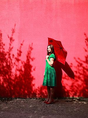 Frau in grün gepunkteten Kleid hält Schirm - p1105m2082585 von Virginie Plauchut