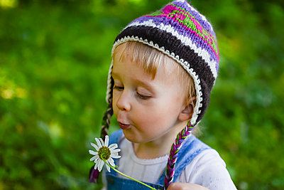 Portrait of little girl wearing knitted hat  blowing flower - p300m2070625 by Petra Silie
