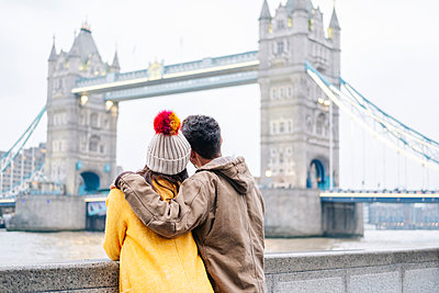 Two young tourists sitting on wall, using smartphone, with  London Bridge in background - p300m2169987 by Daniel González