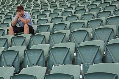 Sad man sitting alone in empty stadium - p301m926838f by Caspar Benson