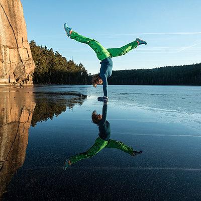 Woman doing yoga on frozen lake - p312m1470652 by Fredrik Schlyter