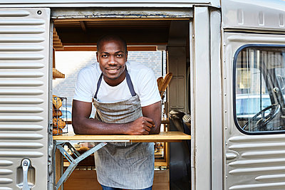 Portrait of confident mid adult male owner standing in food truck - p426m1536948 by Maskot