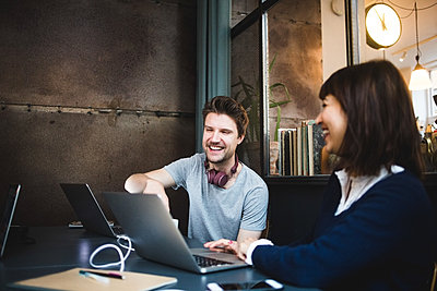 Cheerful female and male entrepreneurs discussing over laptop at desk in office - p426m2089039 by Maskot