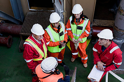 Engineers in brainstorming session on oil rig - p924m1174821 by Okapics