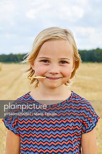 Mädchen auf einem Strohfeld - p1540m2200507 von Marie Tercafs