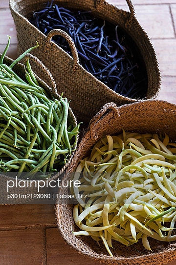 Fresh harvested variety of yellow, green and purple beans in straw baskets - p301m2123060 by Tobias Titz