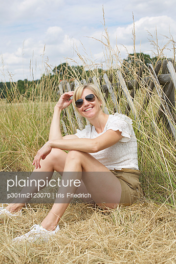 Portrait confident, carefree woman sitting in tall grass - p301m2123070 by Iris Friedrich