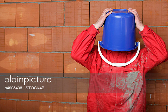 Building worker wearing a pail over his head