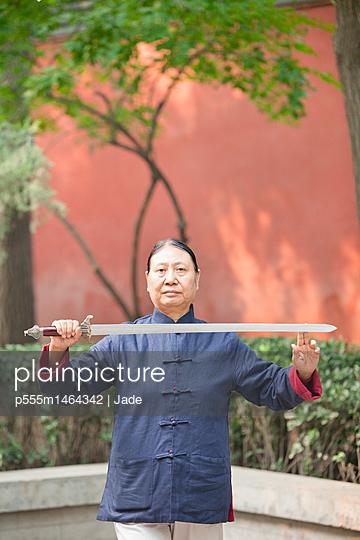 Older Chinese man practicing taiji in park