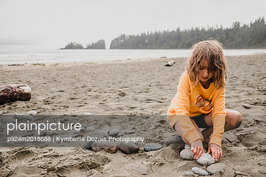 Girl playing on beach, Tofino, Canada - p924m2018688 by Kymberlie Dozois Photography