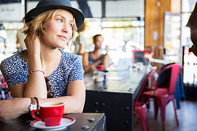 Pensive woman in hat with coffee looking away in cafe - p1023m1146493 by Sam Edwards