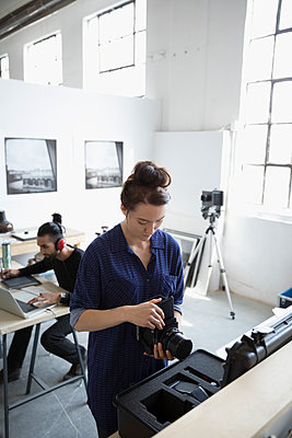 Female photographer working with digital camera and lens in art studio - p1192m1490281 by Hero Images