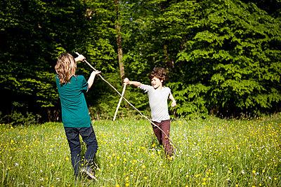 Jungen beim Stockkampf im Park - p1195m1138139 von Kathrin Brunnhofer