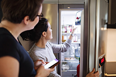 Woman with mobile phone looking at girlfriend opening refrigerator in kitchen - p426m1579973 by Maskot