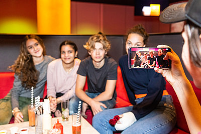 Cropped image of teenage boy photographing multi-ethnic friends sitting on sofa at restaurant - p426m1588376 by Maskot