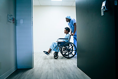 Nurse pushing boy in wheelchair - p555m1532472 by FS Productions