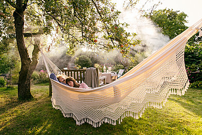 Couple relaxing in hammock - p788m2031178 by Lisa Krechting