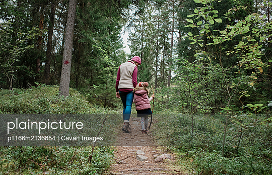 mother holding her daughters hand walking through the forest in fall - p1166m2136854 by Cavan Images