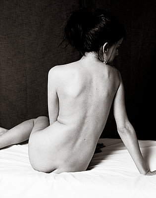 Back of classic nude female sitting on a bed leaning on one arm with her legs up beside her body. - p1433m1516687 by Wolf Kettler
