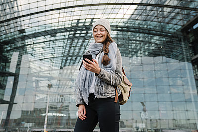 Happy young woman using smartphone at the central station, Berlin, Germany - p300m2155171 by Hernandez and Sorokina
