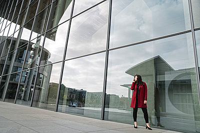 Businesswoman standing near to modern building and using smartphone - p300m2155197 by Hernandez and Sorokina